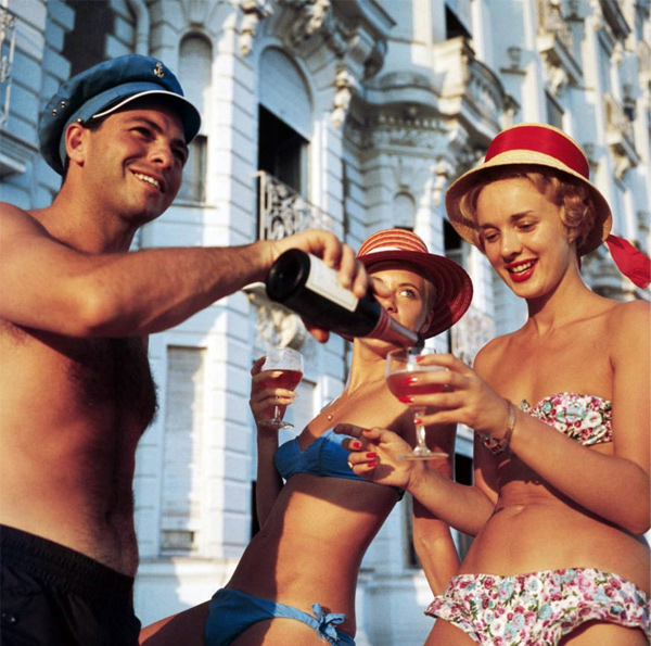 Swimsuited revellers enjoy a glass of wine outside the Carlton Hotel, Cannes, by Slim Aarons